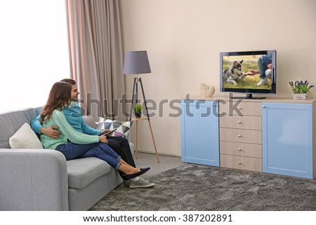 Young couple watching TV on a sofa at home - stock photo
