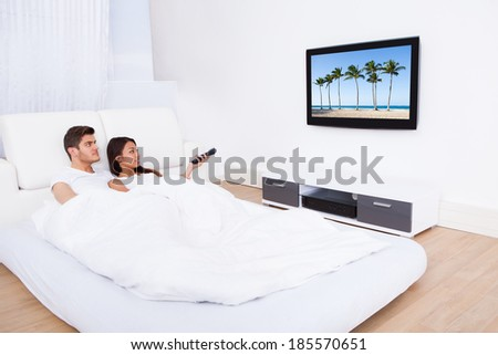 Young couple watching TV while lying in bed at home - stock photo