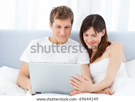 Young couple watching videos on their computer at home - stock photo