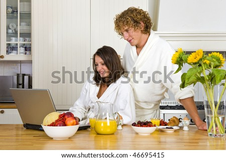 Young couple wearing bath robes enjoying a healthy breakfast in a kitchen behind a laptop - stock photo