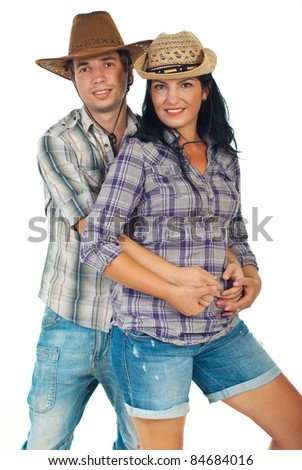 Young couple wearing jeans,squares shirts and cowboy's hats and standing in embrace isolated on white background