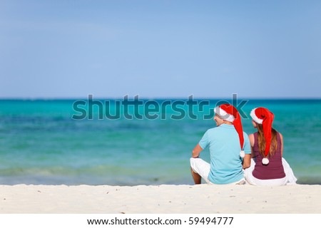 Young couple wearing red Santa hats on  Christmas beach vacation - stock photo