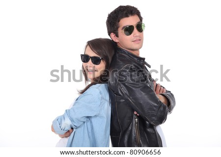 Young couple wearing sunglasses and trendy clothing - stock photo