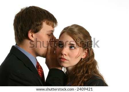 Young couple whispering secrets in workplace - stock photo