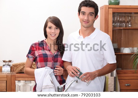 young couple wiping glasses in the kitchen - stock photo