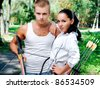 young couple with a bow and arrows in the woods - stock photo