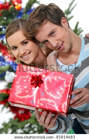 Young couple with a Christmas present - stock photo