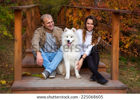 Young couple with a dog on a walk in the autumn forest - stock photo