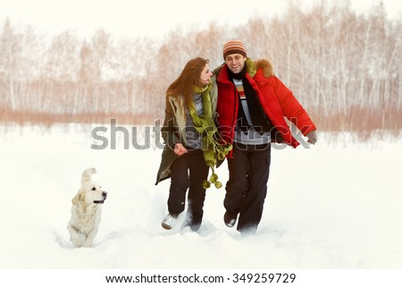 Young couple with a dog on a winter walk. man and woman with labrador outdoors - stock photo