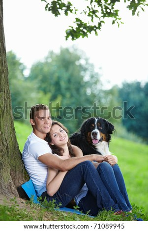 Young couple with a dog outdoor - stock photo