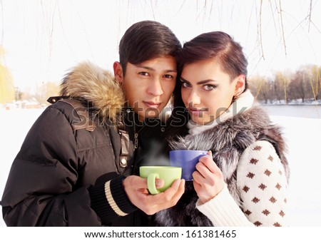 Young couple with a hot drink in winter outdoors