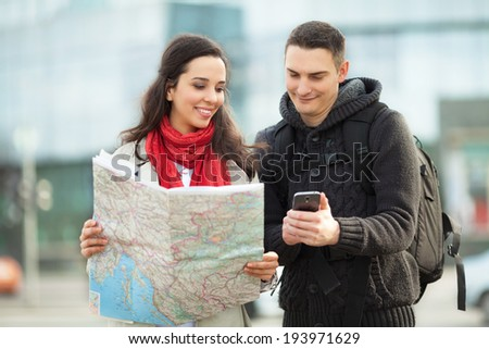 Young couple with a map in a city street. People traveling - stock photo