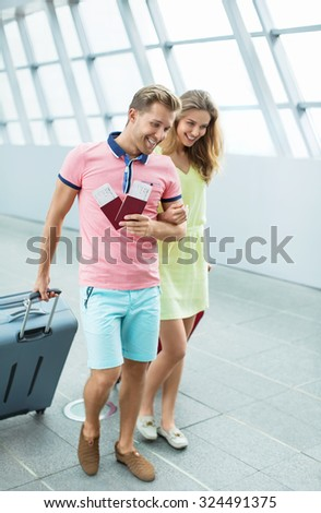 Young couple with a suitcase at the airport - stock photo
