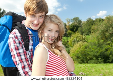 young couple with backpack, hugging and smiling - stock photo