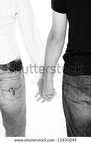 Young Couple with Backs To Camera Holding Hands - stock photo
