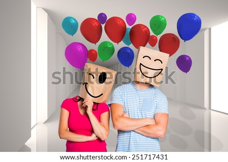 Young couple with bags over heads against digitally generated room with bright light - stock photo