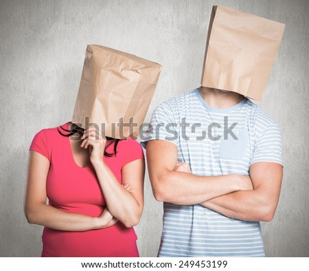 Young couple with bags over heads against weathered surface - stock photo
