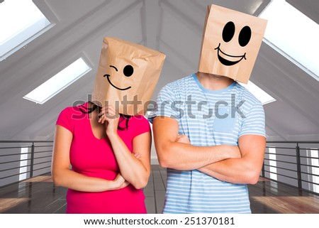 Young couple with bags over heads against white room with skylights - stock photo