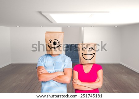 Young couple with bags over heads against white room with stairs - stock photo