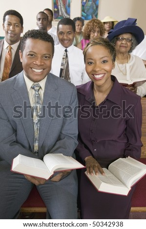 Young couple with Bibles sitting on church pews, portrait - stock photo