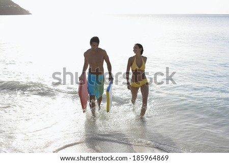Young couple with bodyboards walking in ocean, St. John, US Virgin Islands, USA - stock photo