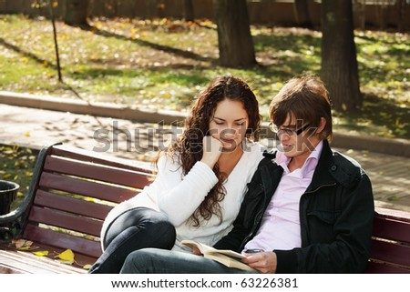 Young couple with book sitting on bench in autumn park