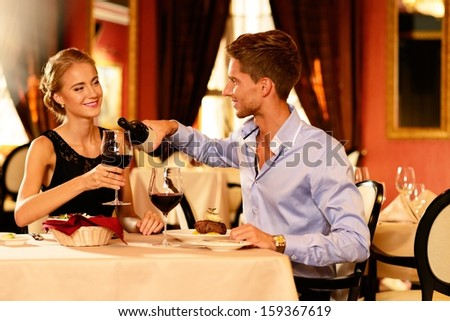 Young couple with bottle of red wine in luxury restaurant - stock photo