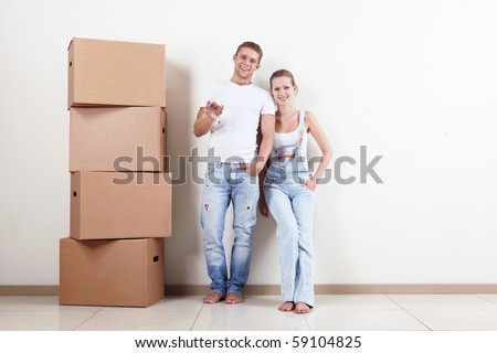 Young couple with boxes and flat keys - stock photo