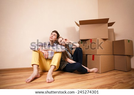 Young couple with boxes dream of a happy life - stock photo