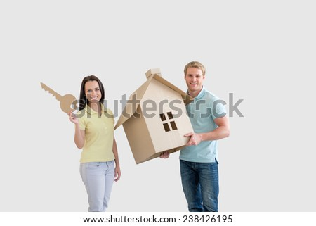 Young couple with cardboard house - stock photo