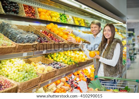 Young couple with cart in store - stock photo
