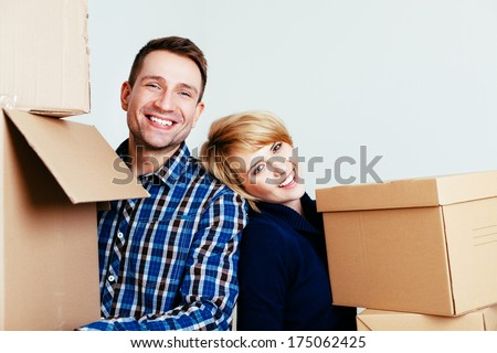 Young couple with carton boxes looking at camera - stock photo