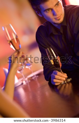 Young couple with champagne glasses in restaurant, celebrating or on romantic date