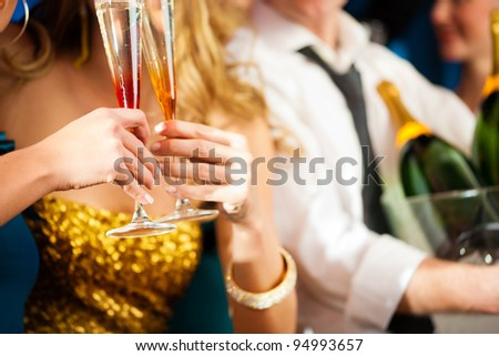 Young couple with Champagner in club or party having fun, close-up - stock photo