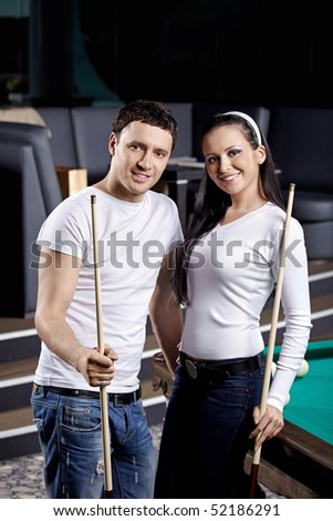 Young couple with cue at a billiard table