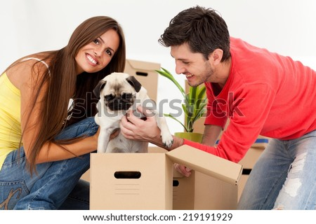 Young couple with dog surrounded by boxes moving into their new home. - stock photo