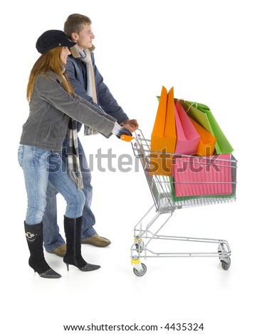 Young couple with full trolley. Smiling and looking straight. Isolated on white in studio. Whole body, side view