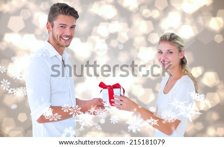 Young couple with gift against light glowing dots design pattern - stock photo