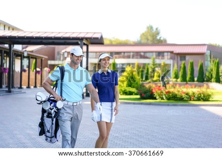 Young couple with golf bag outdoors - stock photo