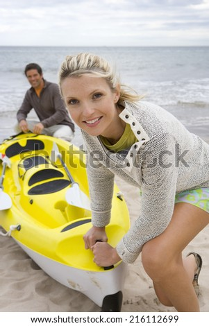Young couple with kayak on beach - stock photo