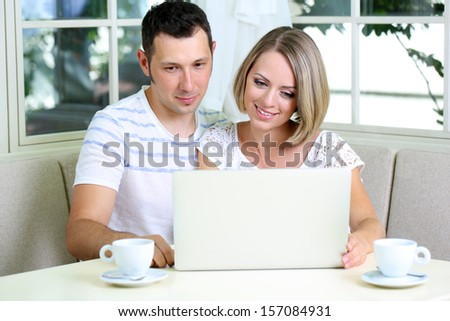 Young couple  with laptop, at home - stock photo
