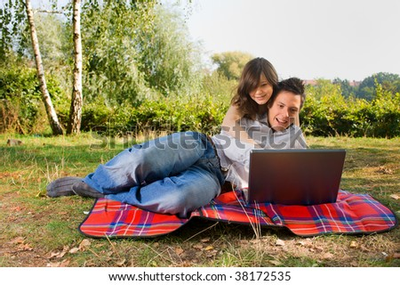 Young couple with laptop at picnic