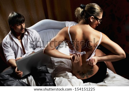 Young couple with laptop lying on bed at home - stock photo