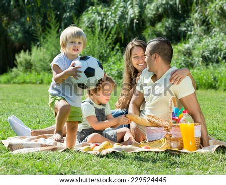 Young couple with little daughters having holiday with picnic. Focus on girl  - stock photo