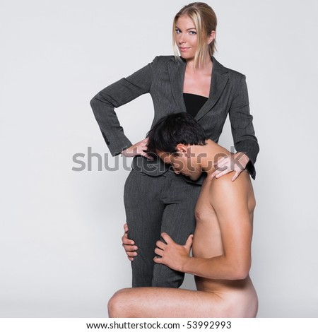 young couple with man naked kneeling in front a woman in studio on isolated grey background - stock photo