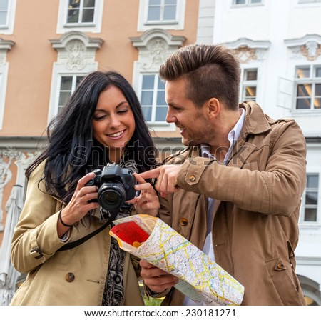 young couple with map and guide during a tour of town on vacation - stock photo