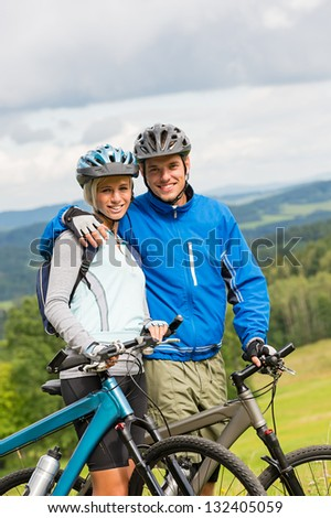 Young couple with mountain bikes enjoying fresh air and nature - stock photo
