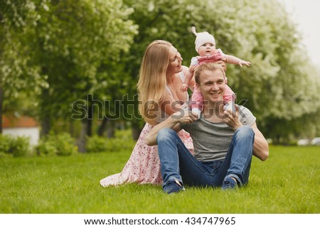 Young couple with newborn son outdoors in spring - stock photo