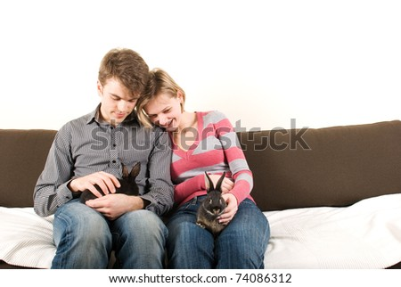 Young couple with rabbits on the couch - stock photo