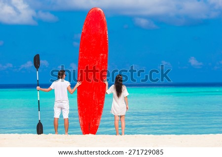 Young couple with red surfboard during tropical vacation - stock photo